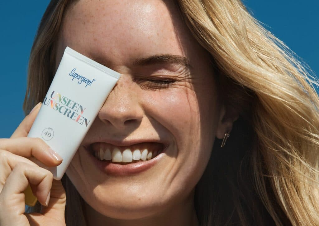 Girl Holding SuperGoop Sunscreen