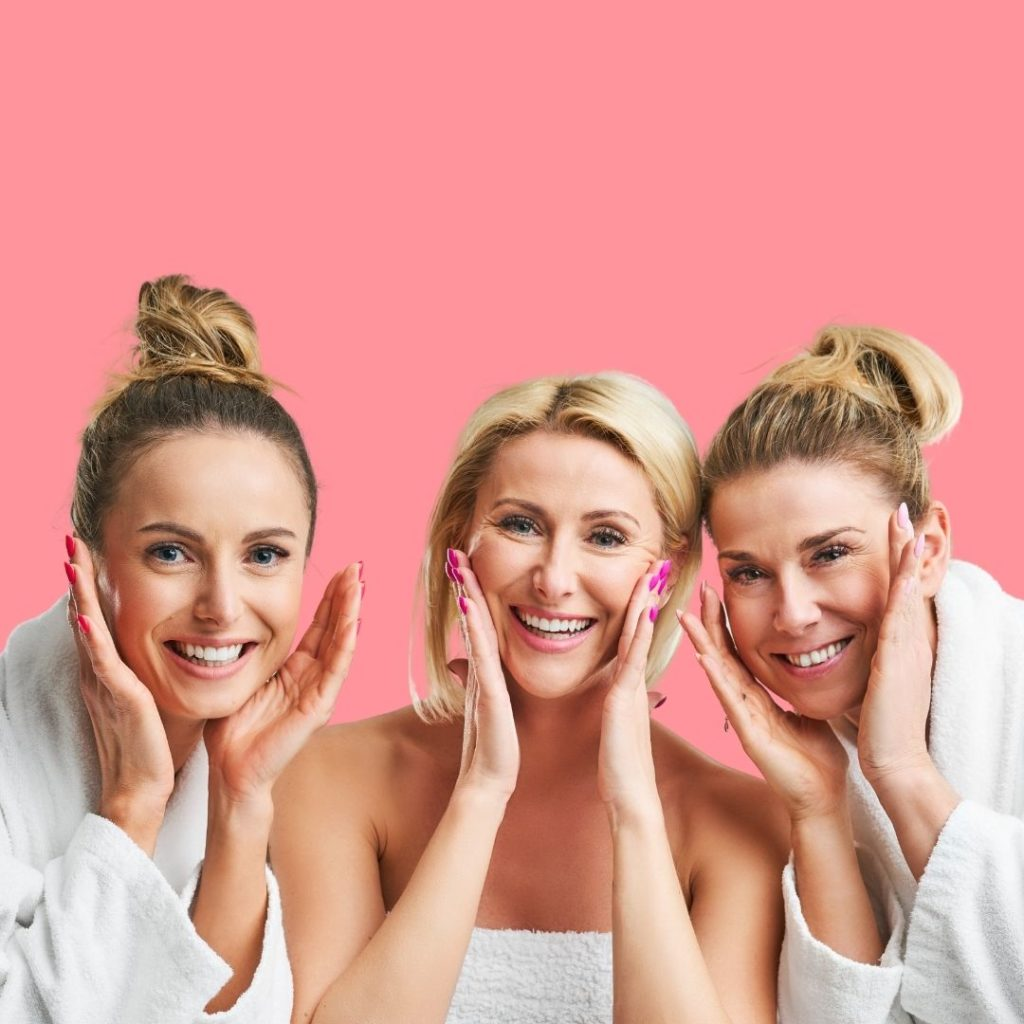 Three women, between the ages of 30-60, looking happy, in bathrobes, taking care of their skin.