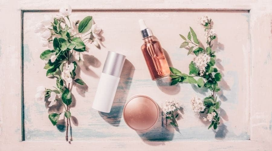 Skincare products, serum, moisturizer, with light pink background and beautiful flowers.